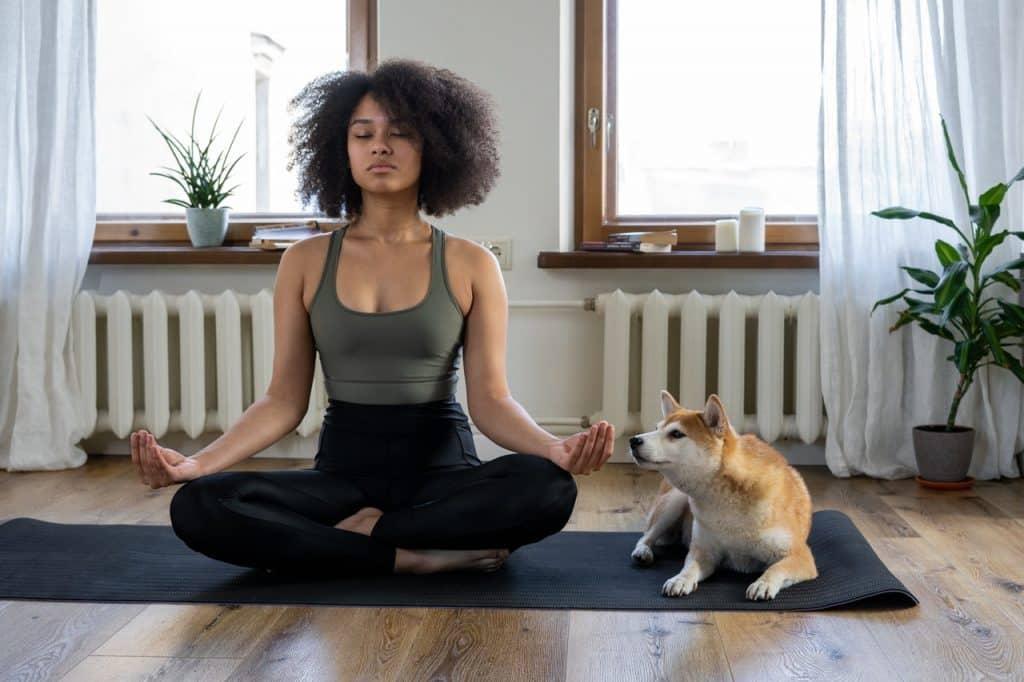 Mulher de cabelos cacheados meditando na sala de estar, ao lado de seu cachorro.