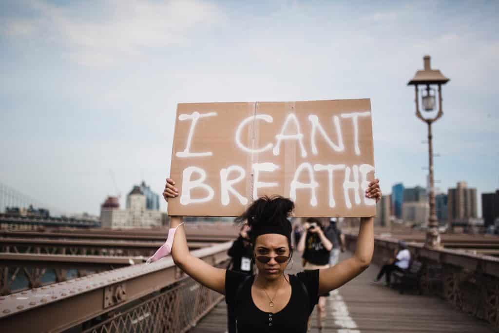 """Mulher negra em um protesto de rua, segurando um cartaz com os escritos """"I can't breathe"""" ou """"eu não consigo respirar"""", em inglês."""