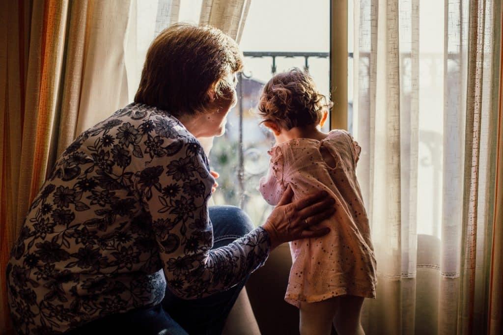 Avó junto a sua neta pequena olhando pela janela, com ambas vistas de costas.