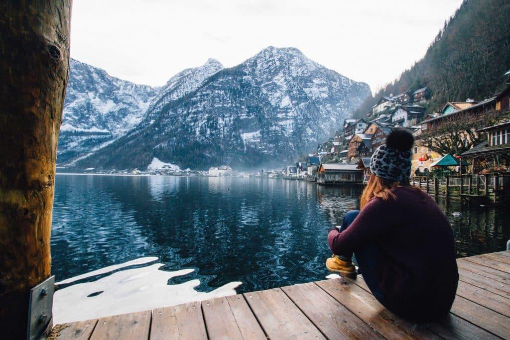 Mulher com roupas de frio sentada num deck olhando montanhas.