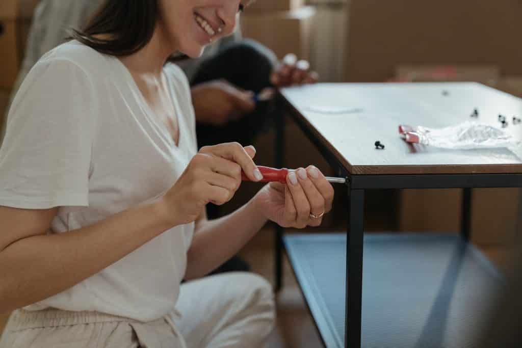 Mulher usando uma chave de fenda em uma mesa