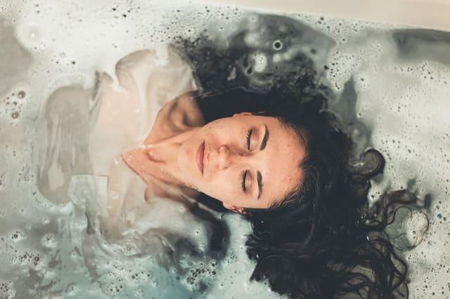 Mulher em banheira vista de cima com olhos fechados