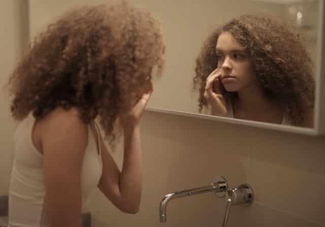 Mulher em frente ao espelho com expressão desanimada
