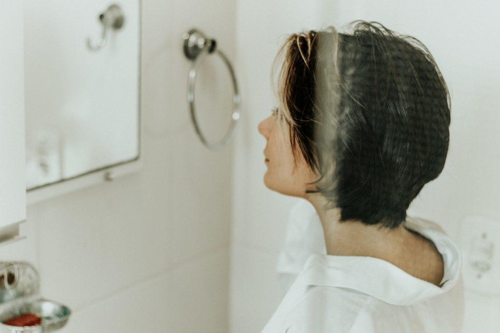 Mulher de cabelos curtos olhando para seu reflexo no espelho de um banheiro.
