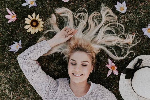 Mulher deitada com cabelos espalhados e flores nos cabelos