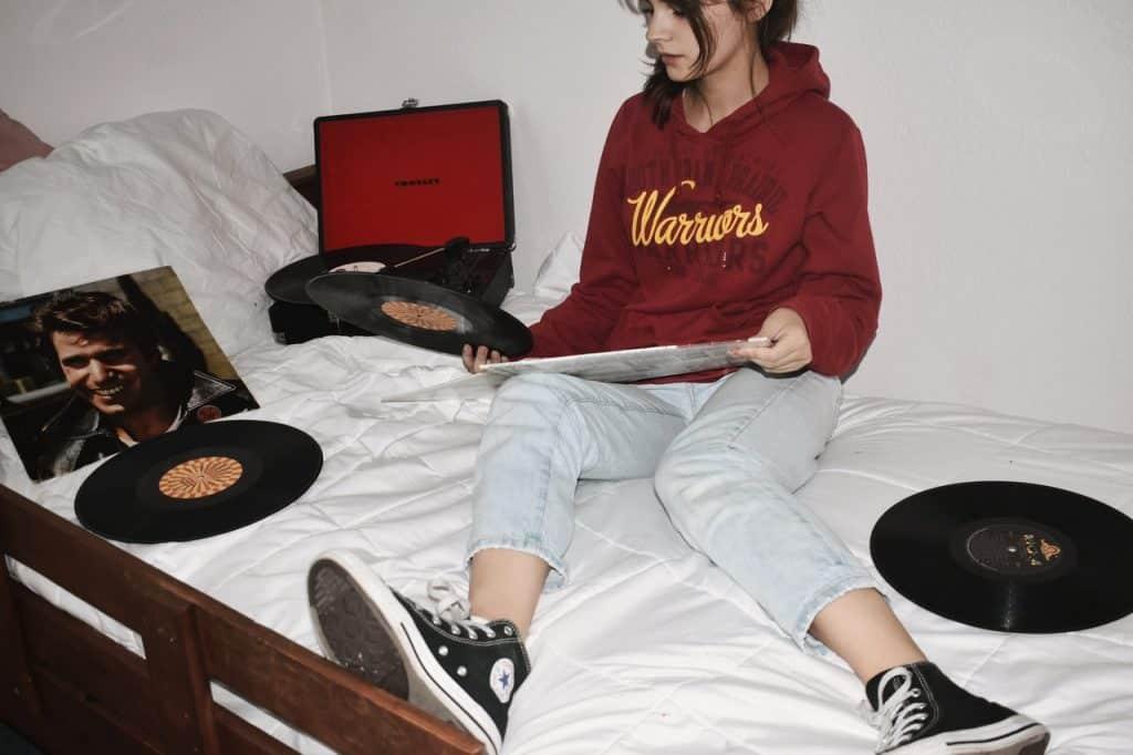 Mulher sentada na cama, com calça jeans e tênis All Star, em meio a discos de vinil.