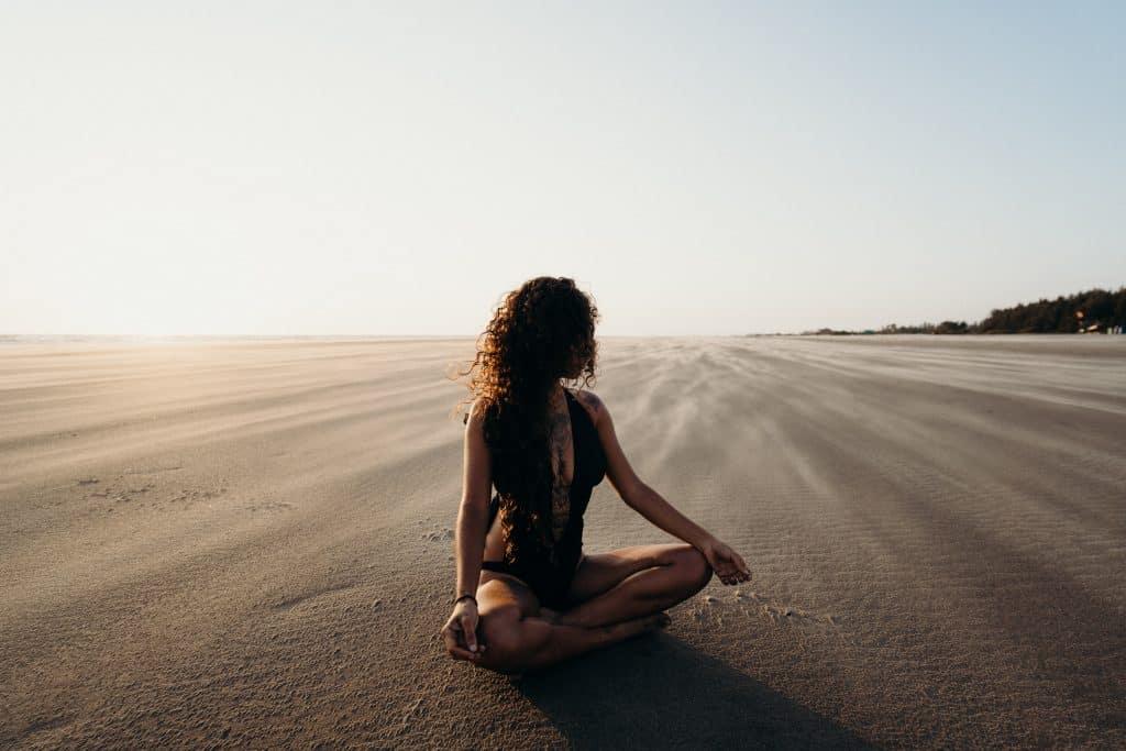 Mulher usando roupas de banho sentada na areia, meditando.
