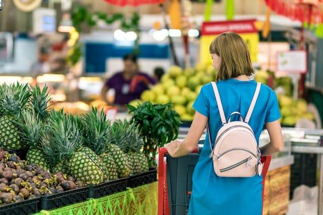 Mulher de costas andando no supermercado escolhendo frutas