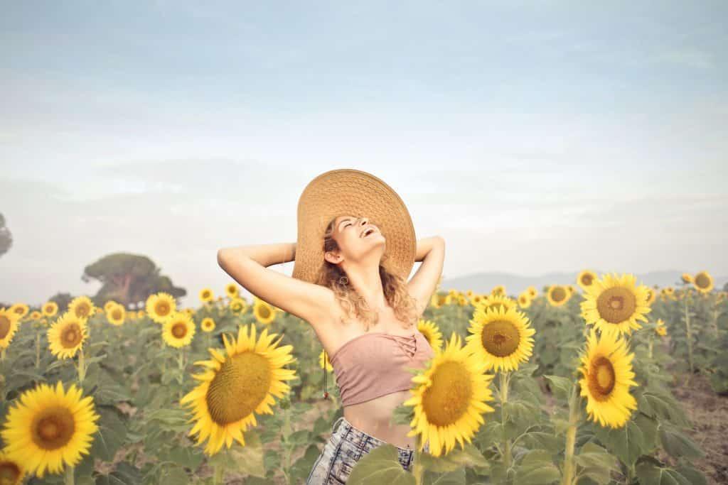 Mulher de chapéu com os braços abertos em um campo de girassóis.