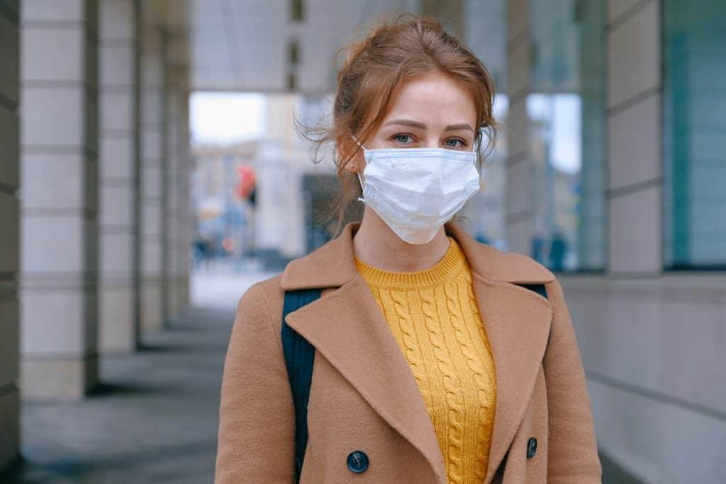 Mulher em ambiente aberto, usando roupas de frio e uma máscara de proteção facial.