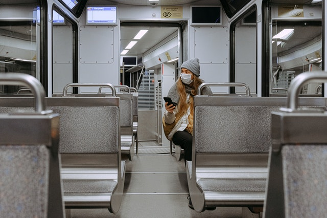 Mulher sentada no fundo de metro usando máscara