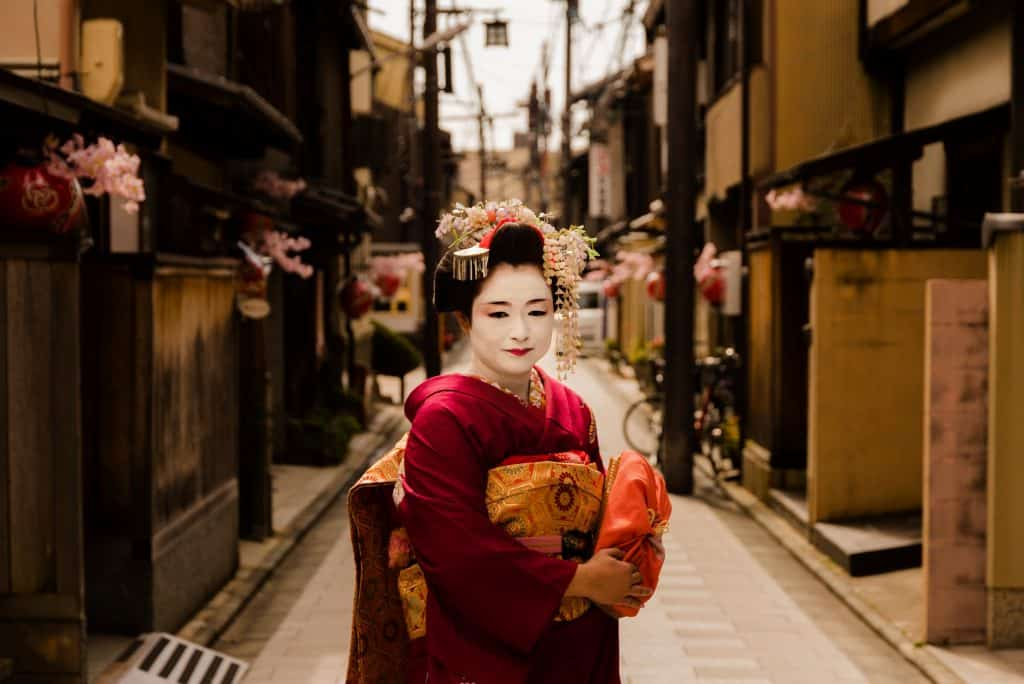 Gueixa vestindo um quimono vermelho em uma rua japonesa.