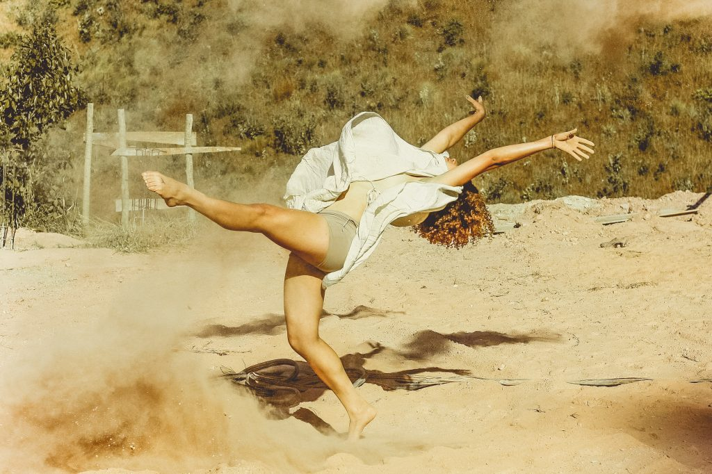 Mulher dançando em um chão de areia.