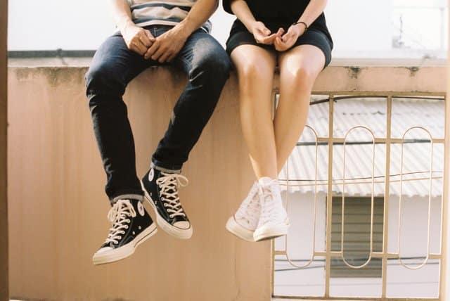 Pernas de casal sentado em muro um do lado do outro