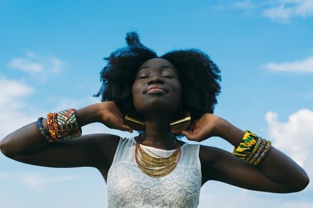 Mulher negra com mãos atras das orelhas e expressão de tranquilidade com céu azul ao fundo