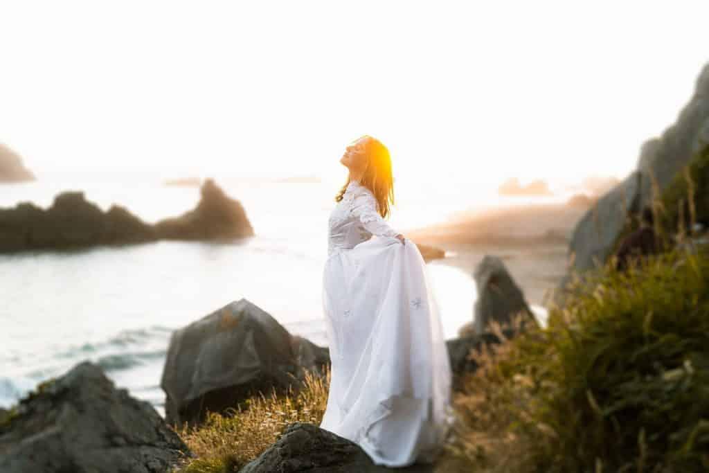 Imagem de uma mulher usando um vestido branco longo. Ela está de frente para o mar e está respirando o ar puro do local.