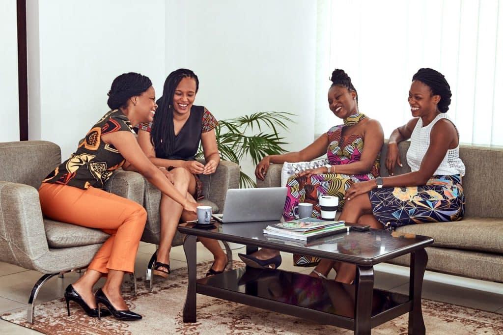 Grupo de quatro mulheres sentadas em em uma sala de estar, rindo e conversando.