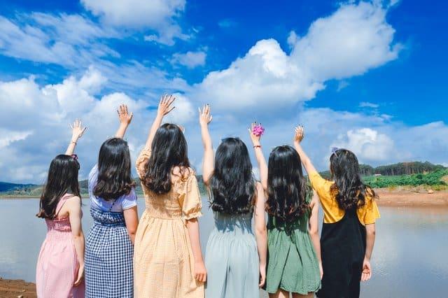 Mulheres de costas em frente lago com mãos para o alto e céu azul ao fundo