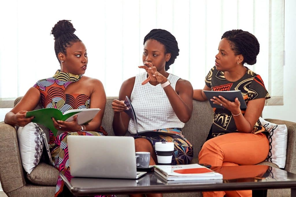Três mulheres sentadas em um sofá, lado a lado, conversando com expressões sérias.