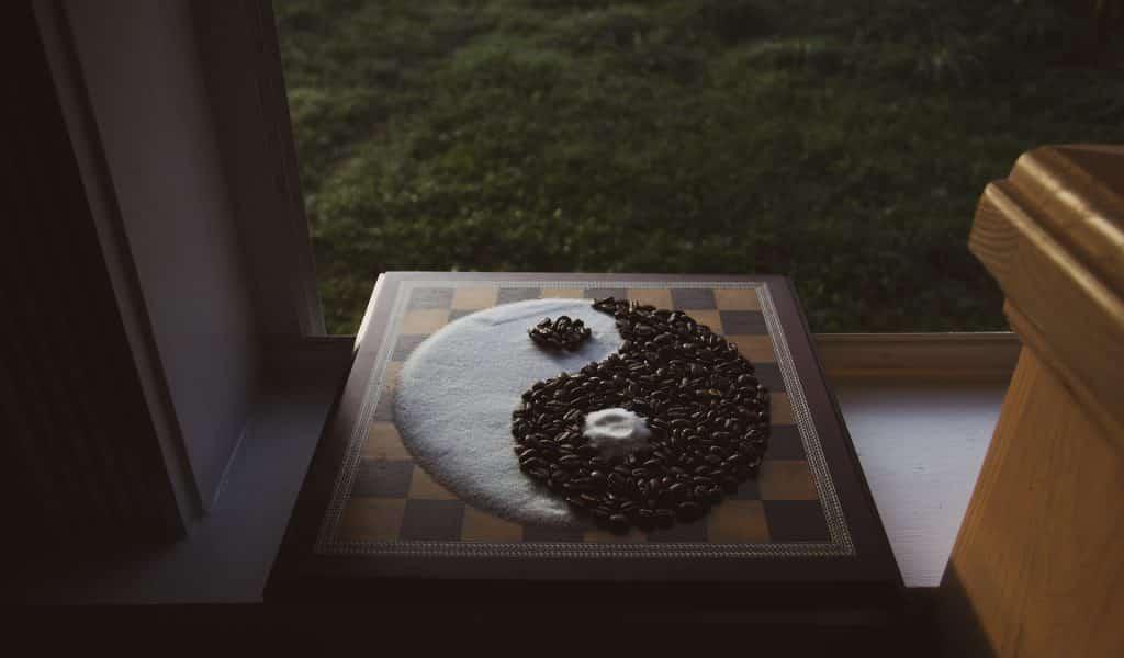 Imagem do símbolo Yin Yang desenhada com grãos de café e açúcar sobre um tabuleiro de xadrez.
