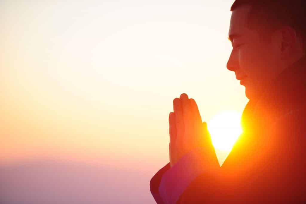 Imagem de um homem oriental com as mãos postas em posição de meditação. Ao fundo, um lindo por do sol.