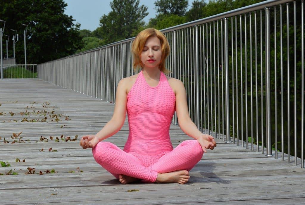 Imagem de uma mulher vestindo um macacão de ginástica na cor rosa. Ela está praticando a meditação.