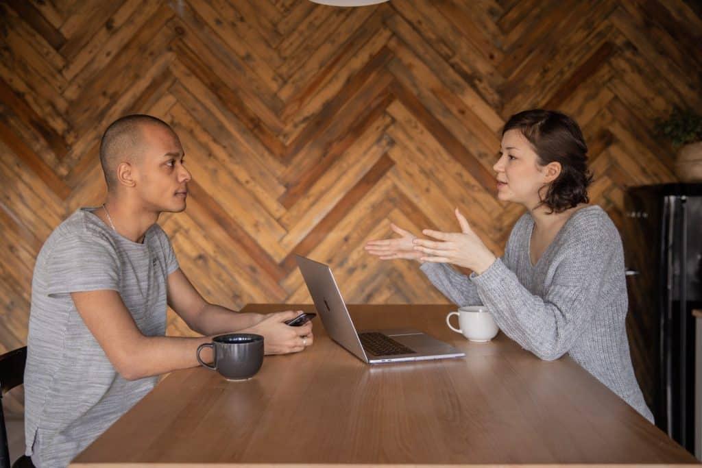 Homem e mulher sentados a uma mesa com um computador, conversando.