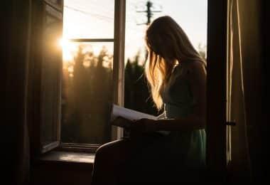 Mulher lendo ao lado da janela com a luz do pôr do sol
