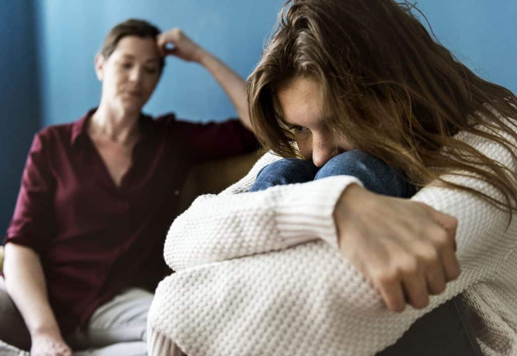 Mulher abraçando suas pernas ao lado de sua mãe