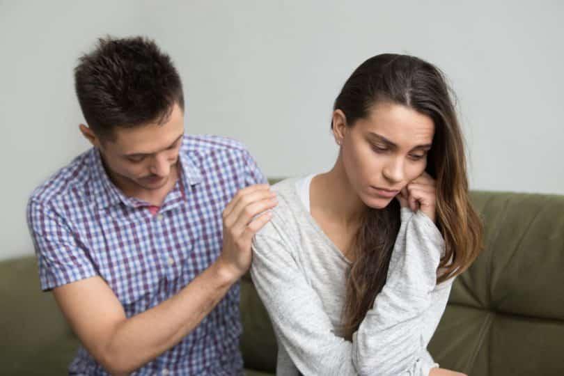 Mulher chateada e homem com mãos no ombro