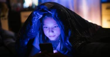Garota embaixo da coberta usando celular