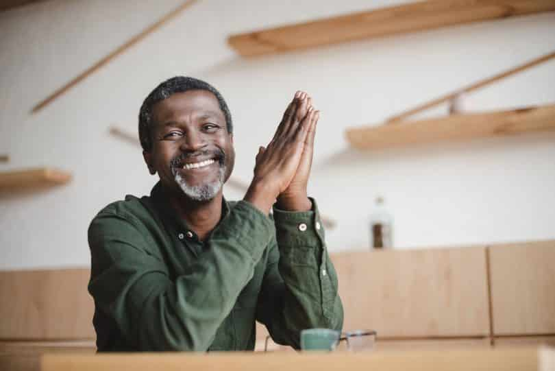 Homem de meia idade sentado à mesa de uma cafeteria, sorrindo.