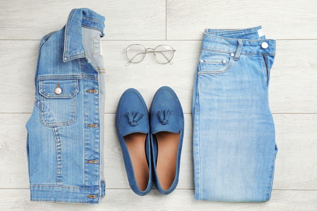 Jaqueta jeans ao lado de um sapato e uma calça azul