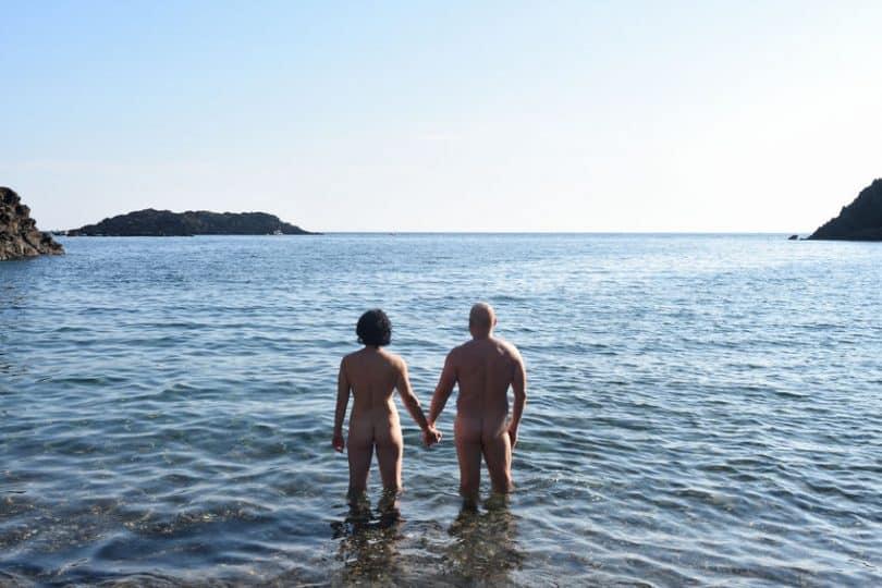 Casal de costas em praia de nudismo de mãos dadas