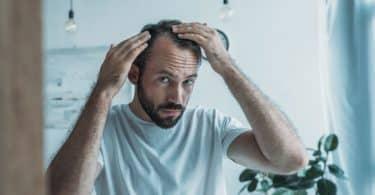 Homem se olhando no espelho mexendo nos cabelos