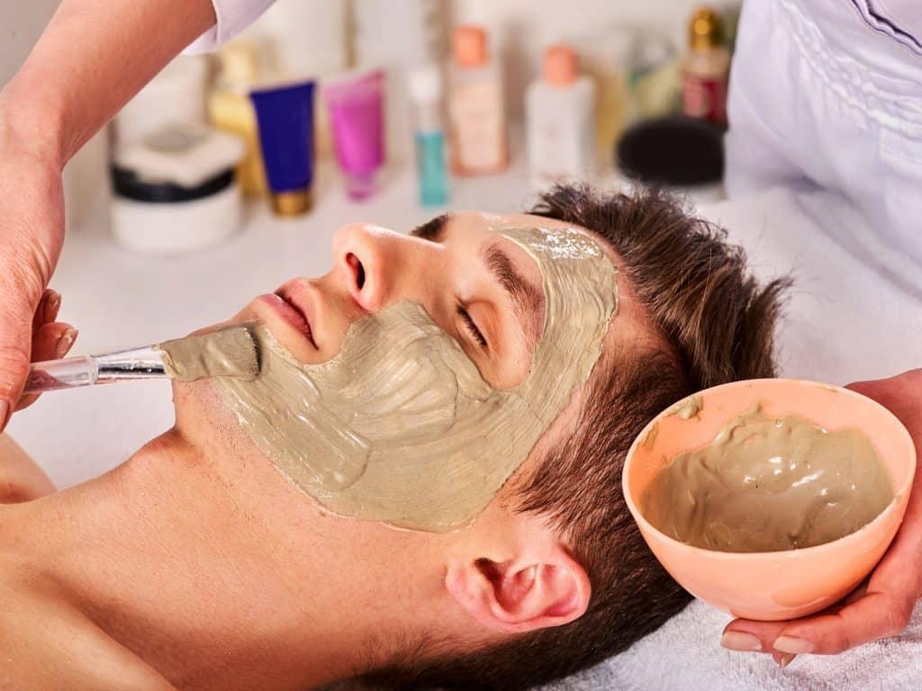 Mulher aplicando argila verde no rosto de um homem