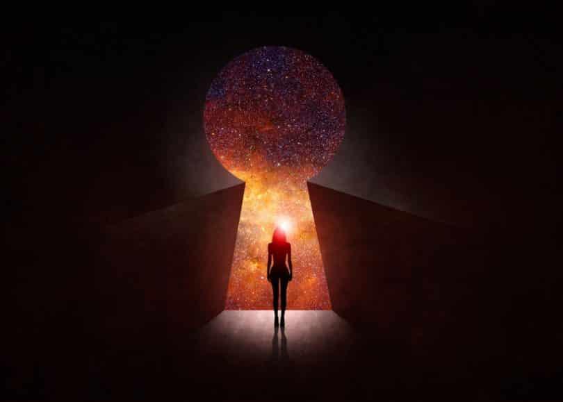 Silhueta de mulher caminhando para fechadura gigante com universo ao fundo