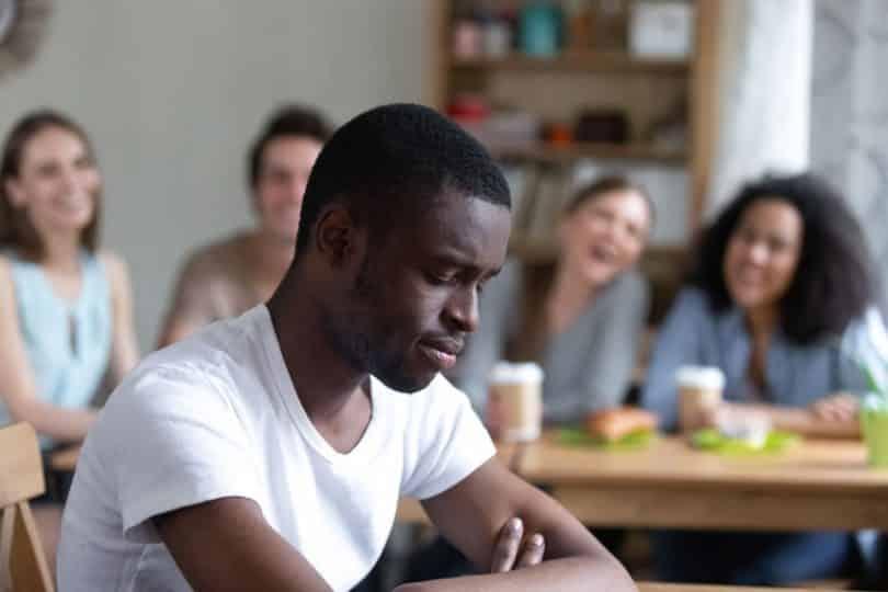 Grupo de pessoas ao fundo rindo de homem negro em foco