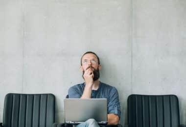 Homem sentado em cadeira com notebook no colo e expressão pensativa