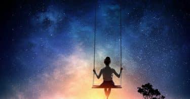 Silhueta de menina em balanço olhando céu estrelado