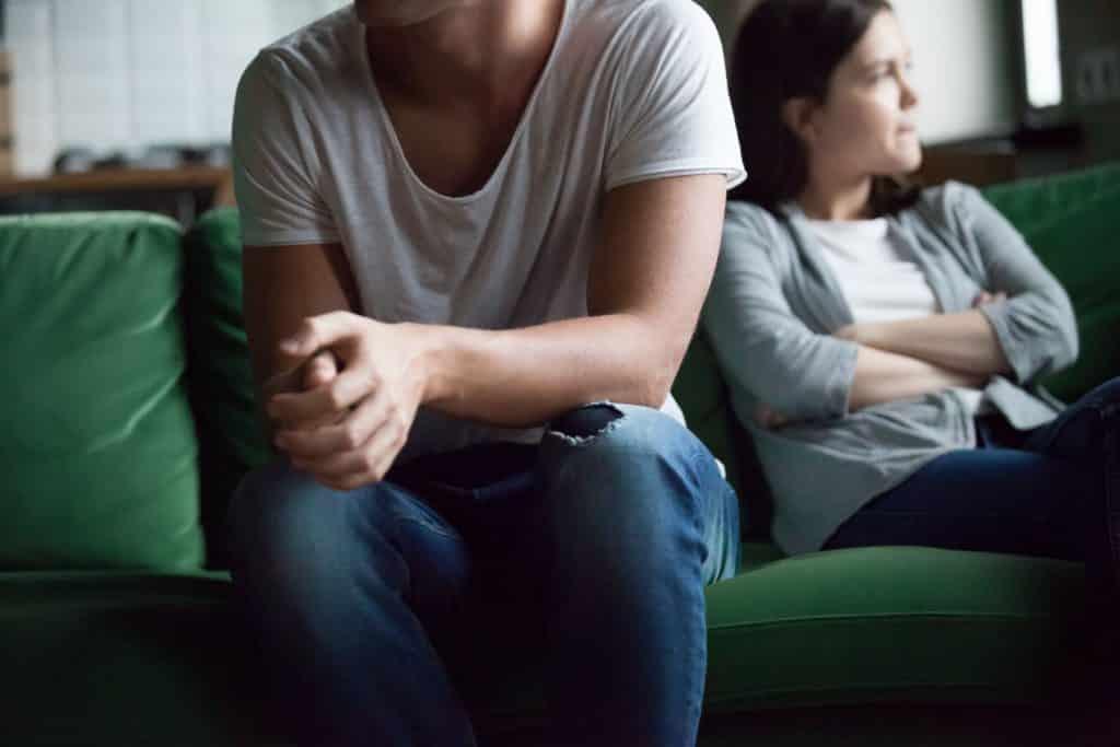 Homem e mulher brancos sentados, mulher com expressão irritada