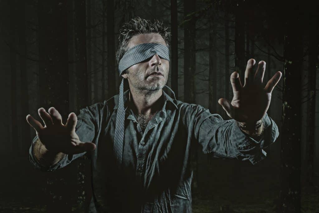 Imagem de um homem representando a situação de um dos atores do filme Bird Box. O homem está com os olhos vendados com a sua gratava cinza.
