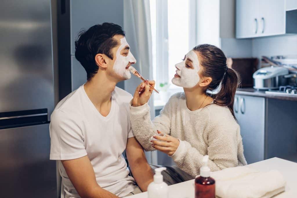 Mulher passando argila branca no rosto do homem a sua frente na cozinha