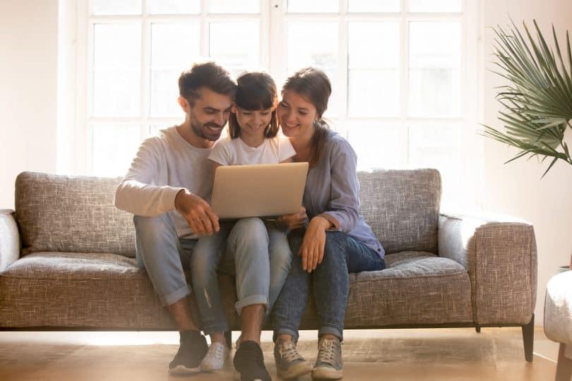 Mãe, pai e filha sentados no sofá, sorrindo e usando o computador.