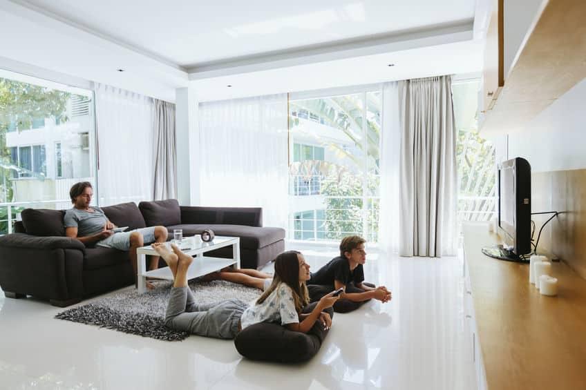 Dois filhos jovens deitados no chão, jogando videogame, enquanto o pai relaxa no sofá.