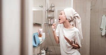 Mulher no banheiro cantando com uma toalha na cabeça e uma escova de dentes na mão.