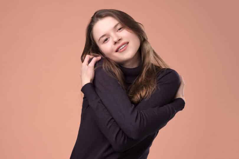 Jovem branca de cabelos médios e castanhos, usando uma camiseta manga longa preta, abraçando a si mesma