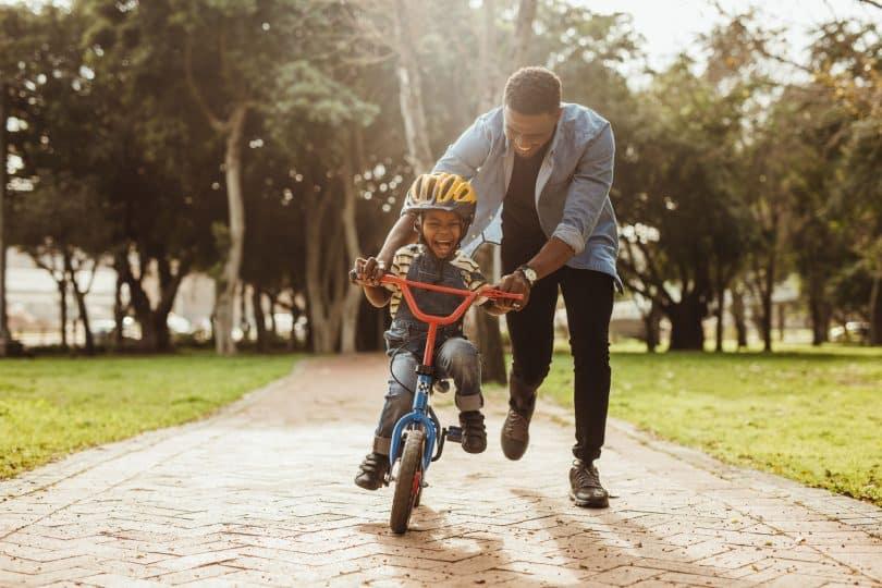 Pai negro ensinando filho a andar de bicicleta ao ar livre
