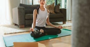Mulher sentada em pose de yoga olhando para o notebook.