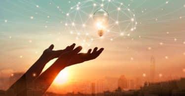 Mãos para o alto com efeito de luzes formando cérebro e lâmpada e sol ao fundo